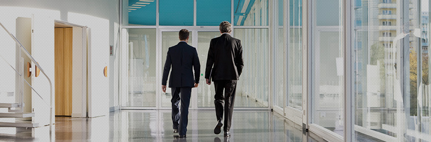 Two businessmen walking down a hallway